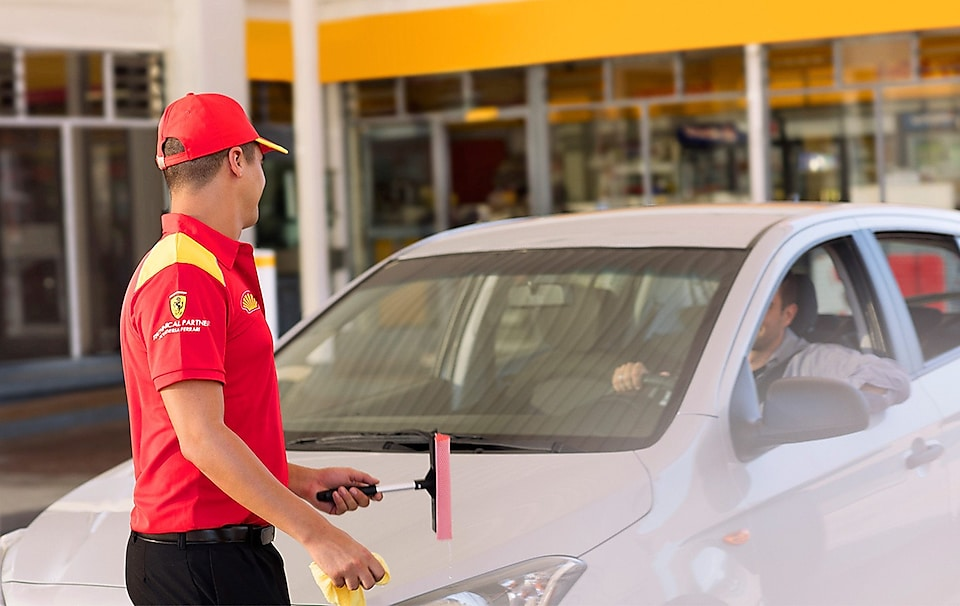 assistant cleaning windscreen of a car